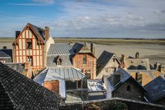 Stone medieval houses with patterns on the walls and roofs in the city of the abbey of Saint Michel. In French Normandy royalty free stock image