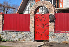 Stone and Metal Red Fence with Door Royalty Free Stock Images