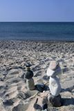 Stone Mom and Pop figures march across beach in East Sandwich, Ma. Beach with many stones under a clear blue,sunny sky. Deep blue ocean with almost no wave royalty free stock photo
