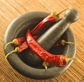 Stone mortar with red chillies Royalty Free Stock Image