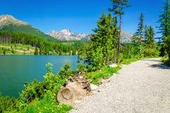 Stone mountain path in high mountains and lake Stock Photos