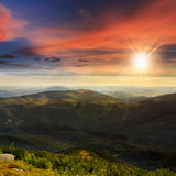 Stone mountain slope with forest at sunset Stock Photos