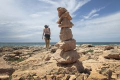 Girl walking next to Stone mounts in the south coast of the island of majorca stock image