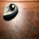 Stone with natural hole on antique wood table. Stock Images