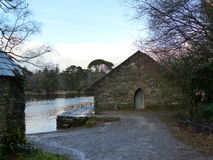 Stone old boathouse by the lake with trees. Stone old boathouse with a path leading up to it by the lake with trees stock images