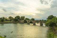Stone old bridge of Artas city Epirus Greece. Sunset colors Royalty Free Stock Photography