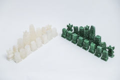 Stone old handmade chess pieces on white background. Shiny green and white transparent stone vintage old handmade chess pieces on white background Stock Photo