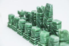 Stone old handmade chess pieces on white background. Shiny green stone vintage old handmade chess pieces on white background Royalty Free Stock Images