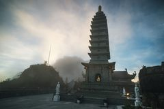 Stone Pagoda in Temple in the fog against the blue sky with dark clouds. on Fansipan mountain peak highest mountain in Indochina. Stone Pagoda in Temple in the royalty free stock image
