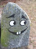 Stone with painted happy face Royalty Free Stock Images