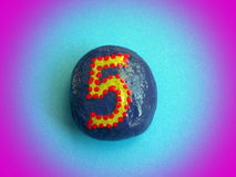 Stone with painted number five Stock Image