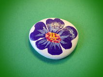 Stone with painted violet flower Royalty Free Stock Photos