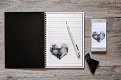 Stone Paper Rewritable Notebook and Smartphone. Top view of stone paper reusable, wipeable, rewritable notebook with pen and wipe cloth, digitizing creativity Stock Image