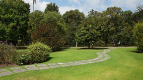 Stone path across the garden with trees in the background. Garden scene Royalty Free Stock Photography