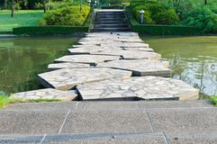 Stone path across the pond. In the park Royalty Free Stock Photography