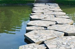 Stone path across the pond. In the park Stock Photography