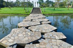 Stone path across the pond. In the park Stock Photo