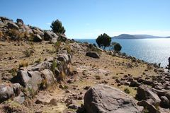 Stone path among bordered fields going down to the Titicaca lake in the sunny day Royalty Free Stock Images