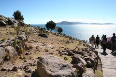 Stone path among bordered fields going down to the Titicaca lake in the sunny day. Tourists group is walking Stock Image
