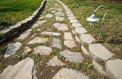 Stone path in garden. A stone path winding through a garden. Stones are surrounded by grass, crabgrass, and weeds. There is a light present royalty free stock images