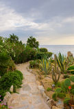 Stone path in the garden against the sea Royalty Free Stock Image