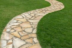 Stone path on green grass in the garden. Home decoration concept royalty free stock image