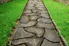 Stone path through a green grassy Stock Photos