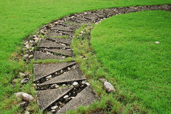 Stone path through a green lawn Stock Photos