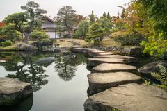 Stone Path Perspective at Koko-en Gardens in Himeji, Japan. Perspective with large flat rocks forming a path over the pond and with a stone lantern and a stock photos
