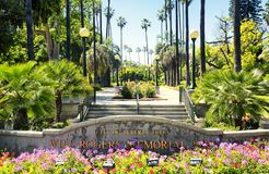 Will Rogers Memorial Park in Beverly Hills California. A stone path surrounded by palm trees behind the Will Rogers Memorial Park sign in Beverly Hills royalty free stock photography