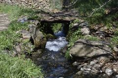 Stone path with wooden bridge over acequia royalty free stock image