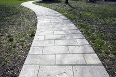 Stone Pathway. The stone pathway leads to somewhere.  It is a grassy area and the slightly windy path, leads off the photograph Royalty Free Stock Photography