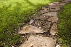 Stone Pathway. A stepping-stone pathway surrounded by green grass Stock Photos