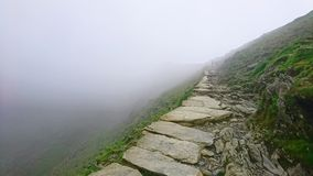 Stone pathway disappearing to vanishing point with drop over edge into fog high up at narrow point on PYG trail on Mount Snowdon i stock images