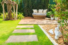 Stone pathway on lawn in the garden. Stone pathway on lawn in the garden with sofa and nature background Royalty Free Stock Photography