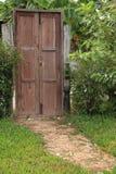 Stone pathway leading to wooden door in garden Royalty Free Stock Photos