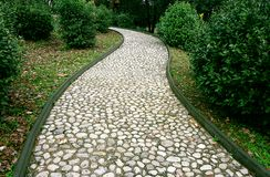 Stone pathway in the park. Stone path made from a pebble. Path surround with green plants Royalty Free Stock Photography