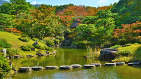Stone pathway on water in autumn rock tree park Royalty Free Stock Photo