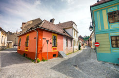 Stone paved old streets with colored houses from Sighisoara fort. Sighisoara, Romania - June 23, 2013: Stone paved old streets with colored houses from Stock Photos