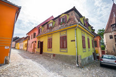 Stone paved old streets with colored houses from Sighisoara fort Royalty Free Stock Photo