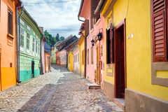 Stone paved old streets with colored houses from Sighisoara fort. Sighisoara, Romania - June 23, 2013: Stone paved old streets with colored houses from Stock Image