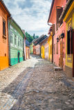 Stone paved old streets with colored houses from Sighisoara fort. Sighisoara, Romania - June 23, 2013: Stone paved old streets with colored houses from Royalty Free Stock Images
