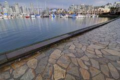 Stone paved seawall path by a marina. False Creek, Vancouver, British Columbia, Canada Royalty Free Stock Photos
