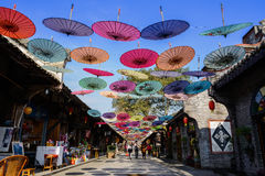 Stone paved street decorated with colorful umbrellas between anc Royalty Free Stock Photography