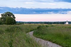 The stone-paved trail through the Bogolubovo meadow towards Church of the Intercession of the Holy Virgin on the Nerl River. Ancient city Vladimir with suburbs Stock Image