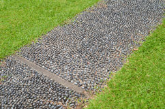 Stone paved walkway with green grass royalty free stock photos