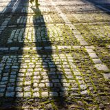 Stone pavement in the sunlight with shadow of man