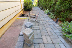 Stone Pavers and Tools for Side Yard Landscaping. Stone Pavers and tiles for side yard patio hardscape with garden landscaping tools rubber mallet sand gravel Royalty Free Stock Photo