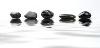 Stone pebbles. A abstract image of black stones reflected in a pool of water Royalty Free Stock Photos