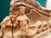 Stone pediment featuring a siren from over an Etruscan tomb entrance. Stone pediment featuring a winged siren from over an Etruscan tomb entrance located at the Royalty Free Stock Photos